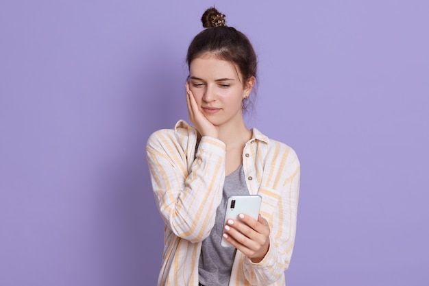 Signora turbata che tiene telefono cellulare nelle mani e che esamina il suo schermo con espressione facciale triste