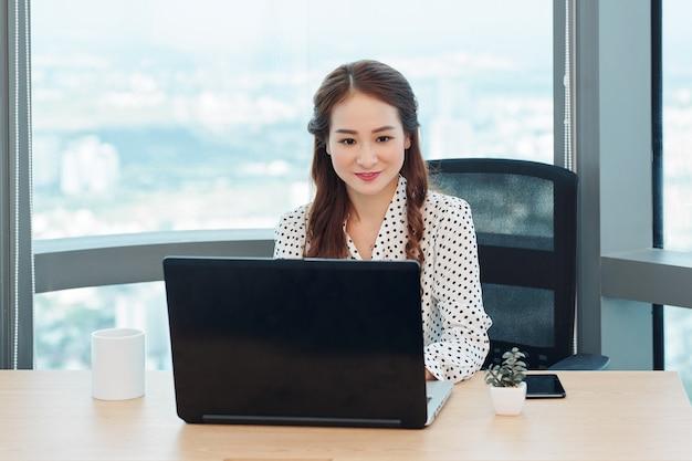 Signora vietnamita di affari che risponde alle e-mail