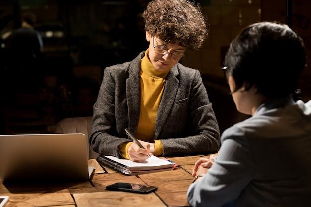 Signore di affari che scrivono piano di lavoro in ufficio scuro