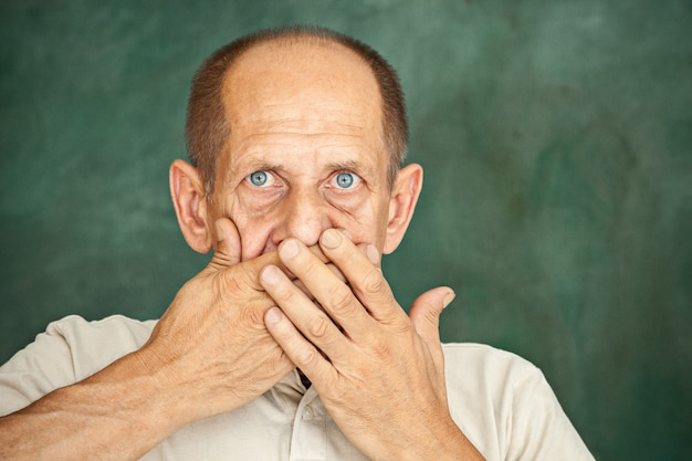 Signore senior colpito che tiene la sua mano contro la sua bocca e che esamina la macchina fotografica sopra