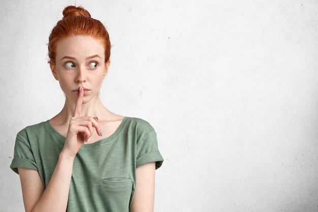 Silenziosa adorabile femmina dai capelli rossi con sguardo sospettoso, cerca di mantenere segrete le informazioni riservate, fa segno di silenzio, isolato su bianco