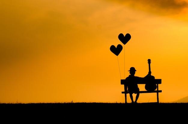 Silhouet di young boy seduto con riempimento da solo. tramonto