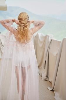 Silhouette della bella ragazza sposa in stand peignoir del balcone con vista sulle montagne