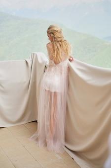 Silhouette della bella ragazza sposa in un peignoir stand del balcone con vista sulle montagne