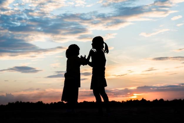 Silhouette di bambini che giocano