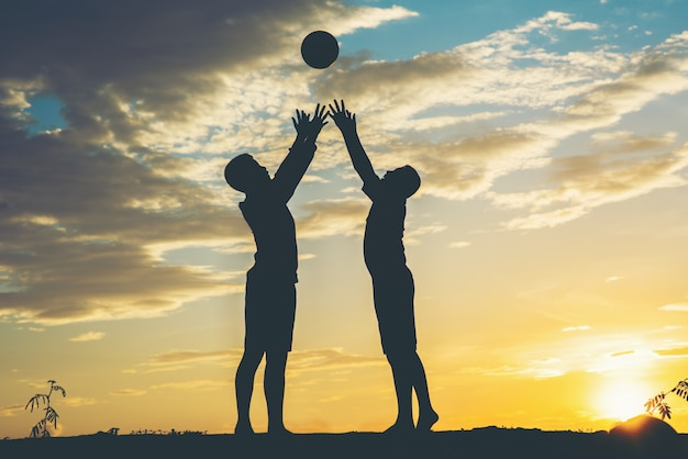 Silhouette di bambini giocano a calcio di calcio
