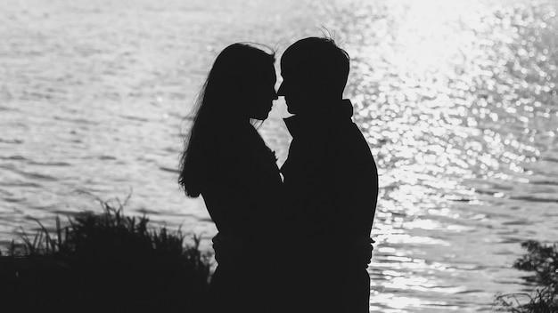 Silhouette di coppia dall'acqua
