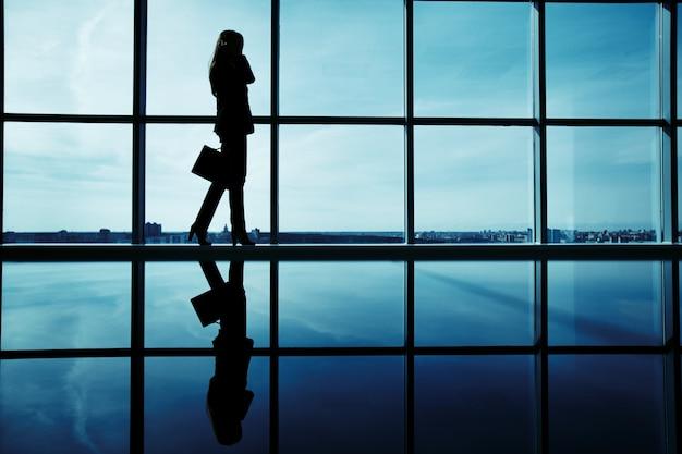 Silhouette di dirigente femminile con valigetta