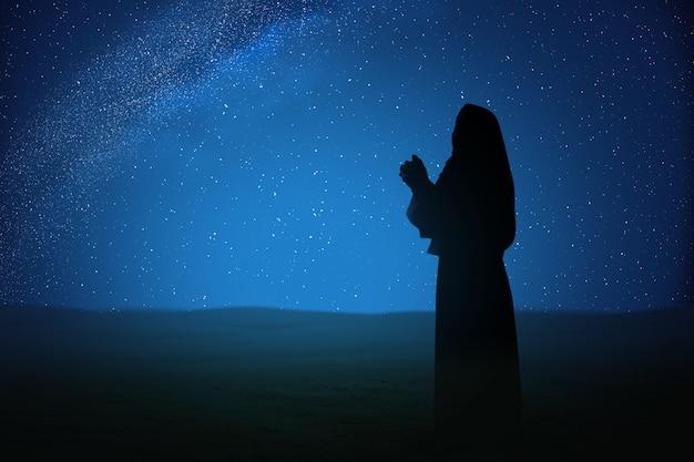 Silhouette di gesù cristo ha sollevato le mani e pregando dio