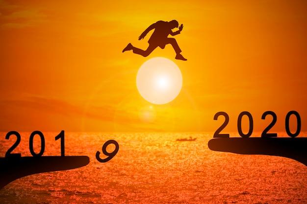 Silhouette di giovane uomo d'affari che salta dal 2019 al 2020