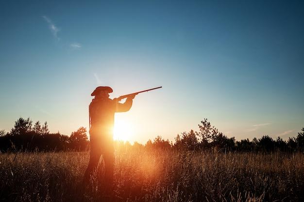 Silhouette di hunter in un cappello da cowboy con una pistola in mano su un bellissimo tramonto