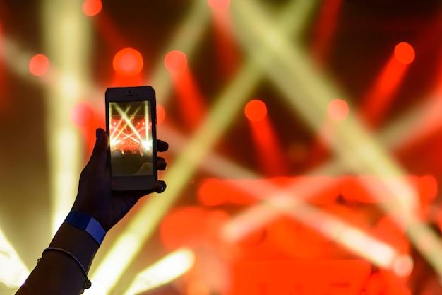 Silhouette di mani con uno smartphone in un concerto