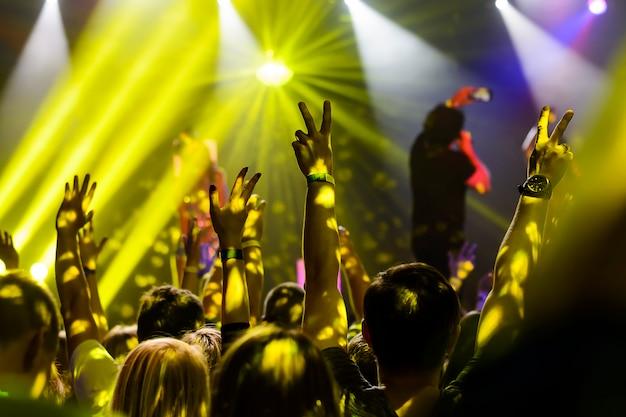 Silhouette di mani in alto al concerto
