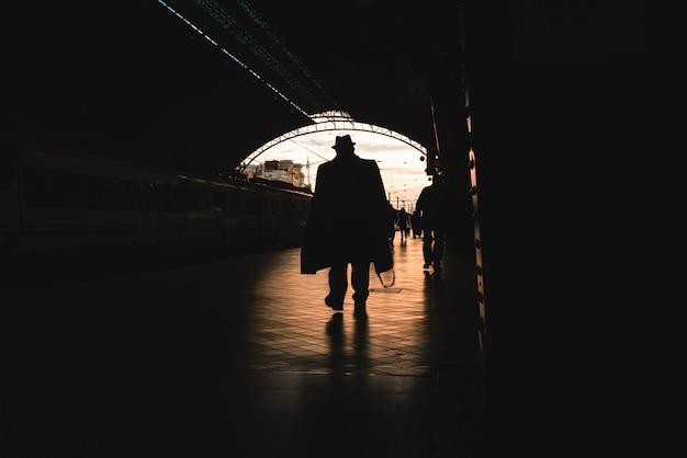 Silhouette di passeggeri in una stazione ferroviaria.