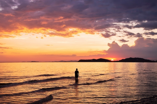 Silhouette di persone che giocano in mare con il cielo al tramonto drammatico