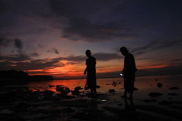 Silhouette di persone in cerca di pesce sulla spiaggia