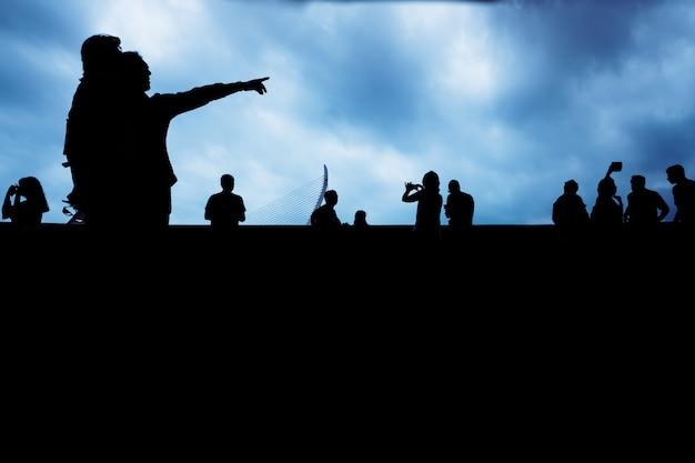 Silhouette di persone irriconoscibili che punta con uno sfondo scuro.
