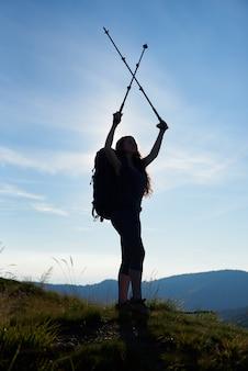 Silhouette di sportiva escursionista femmina con zaino in piedi sulla cima di una collina, tenendo i suoi bastoncini da trekking sopra una testa, contro il cielo blu in montagna