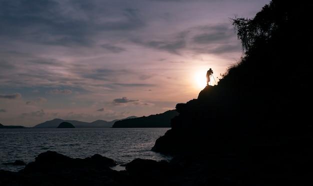 Silhouette di un fotografo o viaggiatore che utilizza una fotocamera dslr professionale