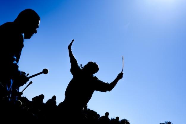 Silhouette di un gruppo di batteristi al sole giocando.
