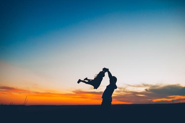Silhouette di un padre e figlia su un tramonto di sfondo