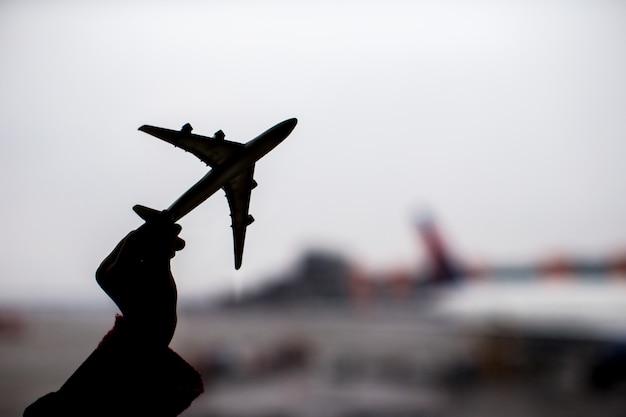 Silhouette di un piccolo modello di aeroplano sullo sfondo dell'aeroporto