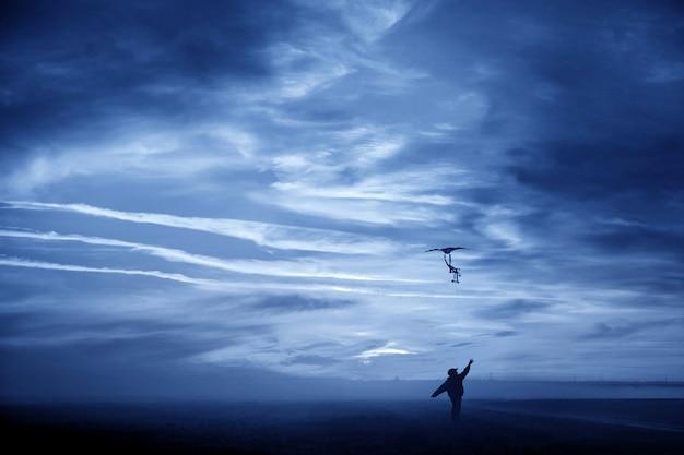 Silhouette di un ragazzo con un aquilone in volo su uno sfondo di cielo blu