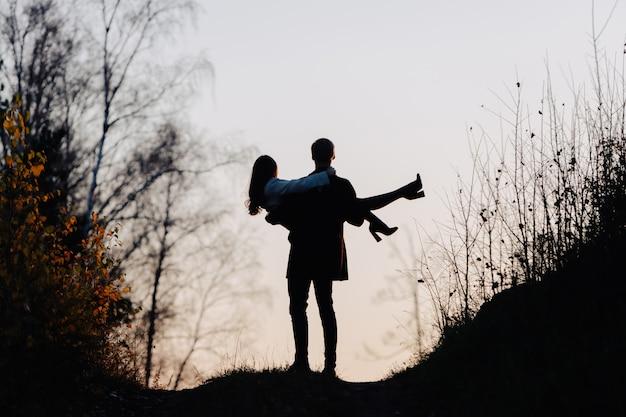 Silhouette di un uomo che tiene una ragazza tra le braccia. vista posteriore.