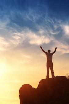 Silhouette di un uomo con le braccia alzate al tramonto