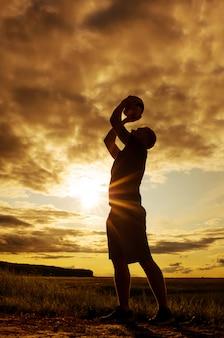 Silhouette di un uomo con una palla.