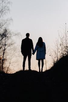 Silhouette di un uomo e una ragazza che si tengono per mano. vista posteriore.
