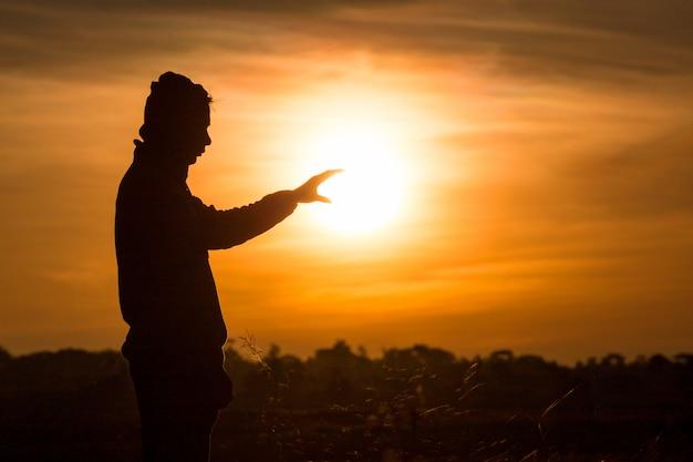 Silhouette di un uomo in piedi e alzare le mani in aria durante il tramonto