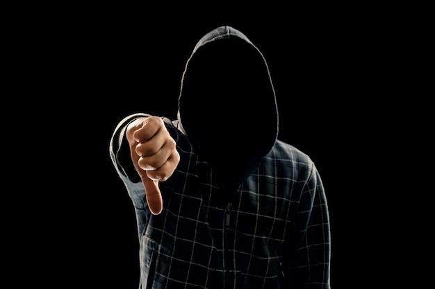 Silhouette di un uomo in un cappuccio su uno sfondo nero il suo volto non è visibile mostrando un pugno