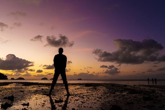 Silhouette di un uomo sulla spiaggia al tramonto