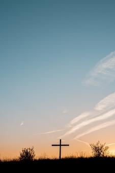 Silhouette di una croce di legno su una collina erbosa con un bel cielo