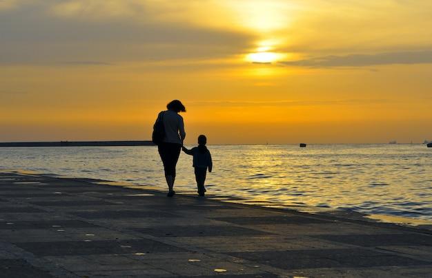 Silhouette di una donna con un bambino, si tengono per mano su uno sfondo di tramonto sul mare