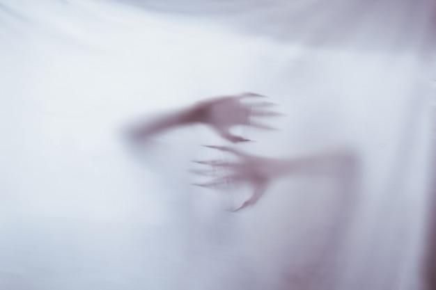 Silhouette di una figura sessuale femminile dietro un vetro nebbioso. concetto dello spirito di poltergeist dall'altro mondo. spaventose mani della morte attraverso il tessuto.