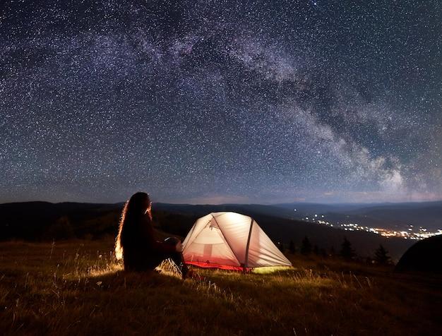 Silhouette di una giovane donna seduta accanto al fuoco e tenda sotto un bel cielo con un sacco di stelle e via lattea godendo il paesaggio di montagne e città di distanza.