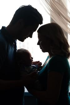 Silhouette di una giovane famiglia con bambino alla finestra