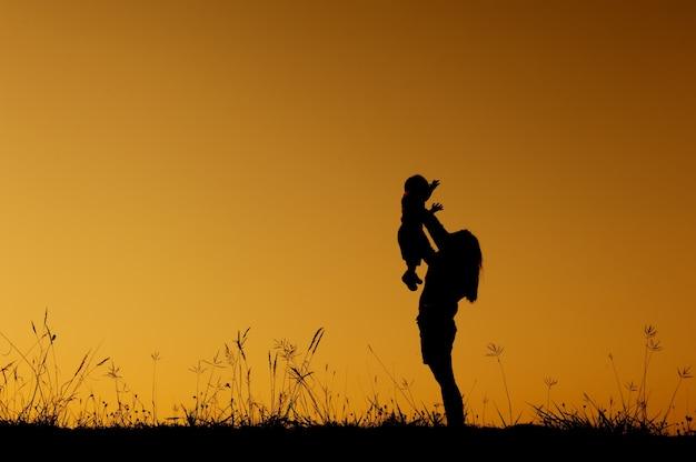 Silhouette di una madre e figlio che giocano nel tramonto