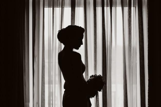 Silhouette di una sposa con bouquet da sposa alla finestra