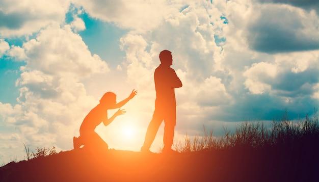 Silhouette di uomo arrabbiato con la moglie in ginocchio