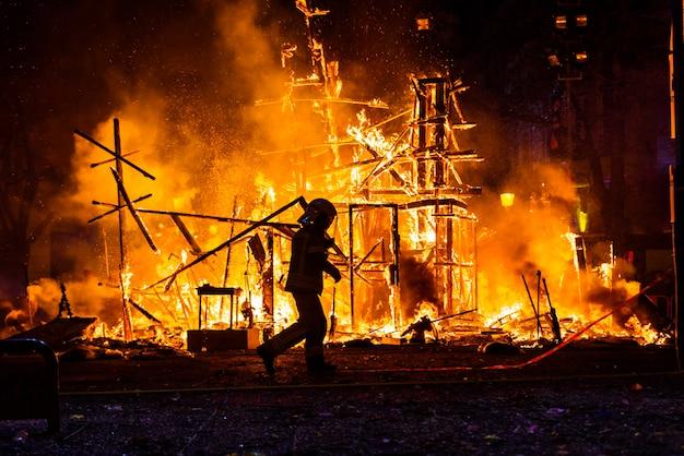 Silhouette di vigile del fuoco cercando di controllare un incendio in una strada durante una notte.