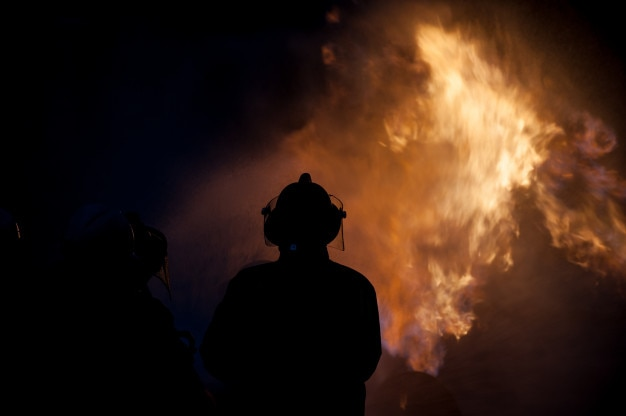 Silhouette di vigili del fuoco che combattono un fuoco infuocato con enormi fiamme di legna che brucia