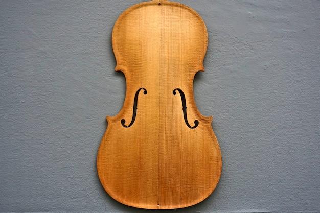Silhouette di violino contro un muro grigio, un segno per un negozio di liutaio.