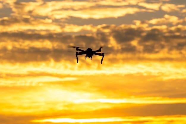 Silhouette drone volando al tramonto