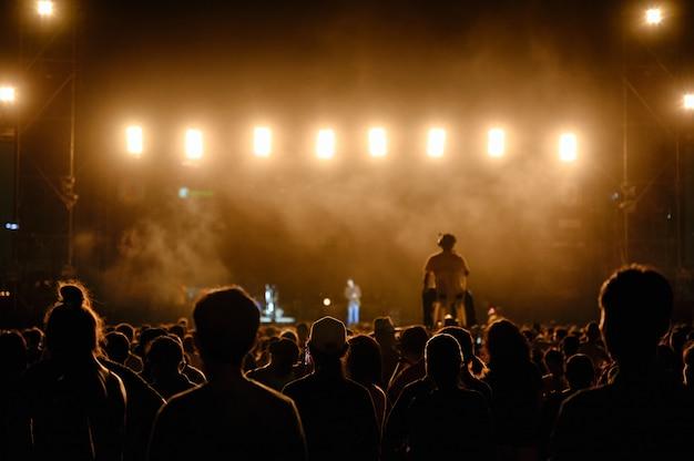 Silhouette il pubblico dei giovani sta guardando il concerto notturno