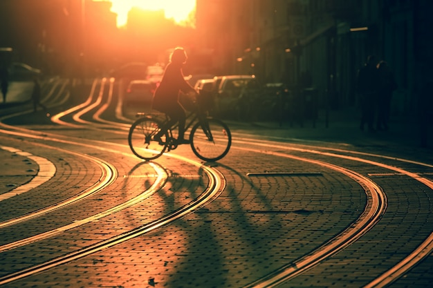 Silhouette sfocata di donna in sella a una bicicletta durante il tramonto nella città di bordeaux in stile vintage