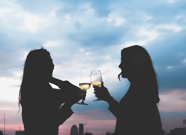 Silhouette two asia lesbian lgbt couple toast champagne glass at rooftop party