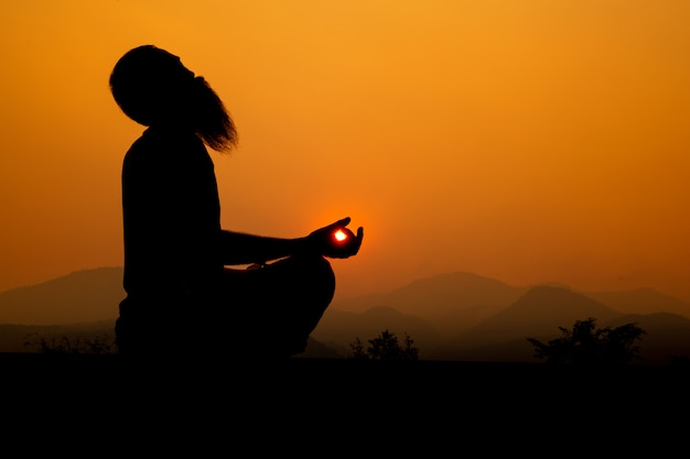 Silhouette - yoga ragazzo sul tetto durante il tramonto, sta praticando yoga.
